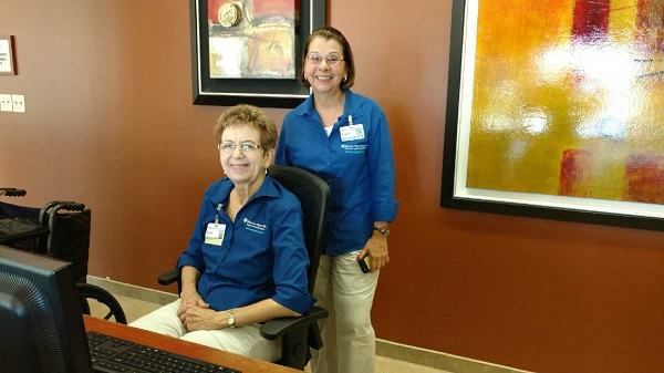 Two BayCare volunteers working at a hospital reception desk