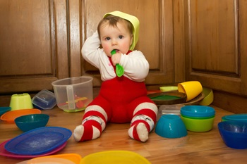 Adorable baby girl pulling pots and pans and other dishes out of a kitchen cupboard