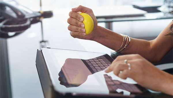 A woman is squeezing a stress ball while sitting in front of her computer.