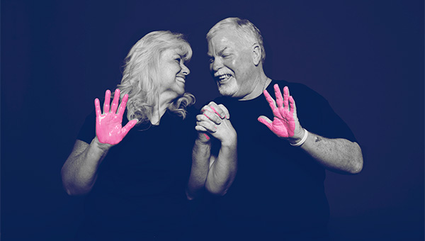 "A senior man and woman participate in the ""It's in Our Hands"" breast cancer awareness campaign."