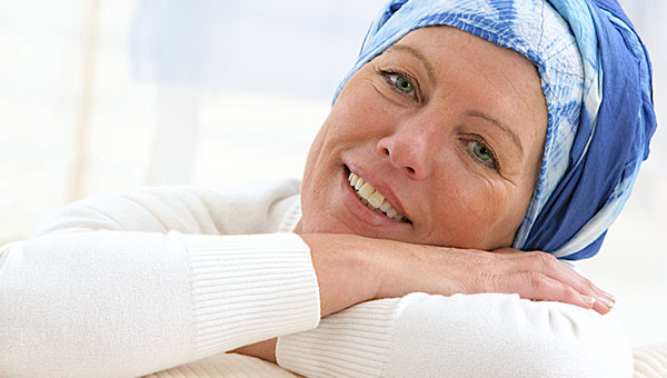 A female cancer survivor is wearing a blue and white scarf on her head.