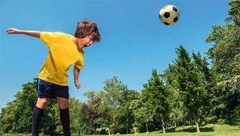 A soccer ball bounces off the head of a boy playing soccer.