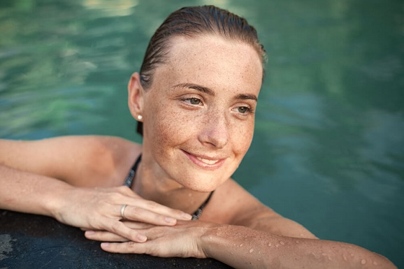 A woman with sun spots is swimming at a pool.