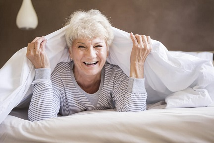 A senior woman is smiling while resting on her bed.