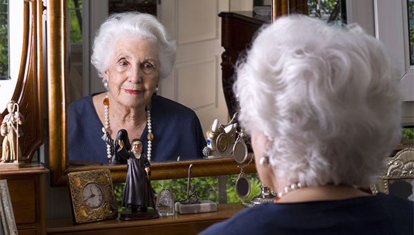 A senior woman is looking at herself in a mirror.