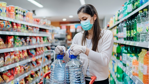 woman wearing mask and gloves adding water jugs to her shopping cart