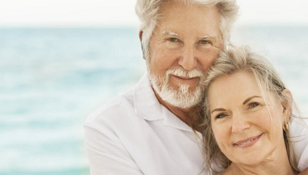 An older couple is spending time together at the beach.