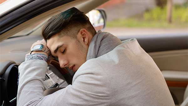 A young man is napping in his car and resting his head on the steering wheel.