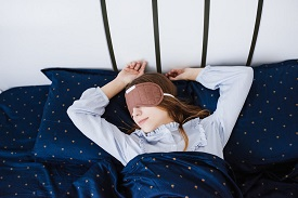 The girl sleeping and lies in her pajamas in a white linens. Blue bed. Blindfold on the head. Sleep mask