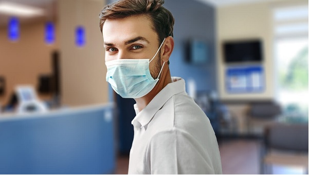 young male wearing a mask standing in an urgent care center