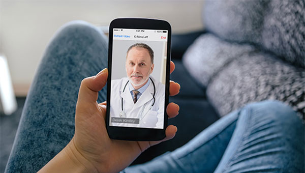 A person is at home on the sofa and using a cellphone for an online doctor visit.