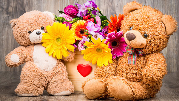 Two teddy bears and flowers