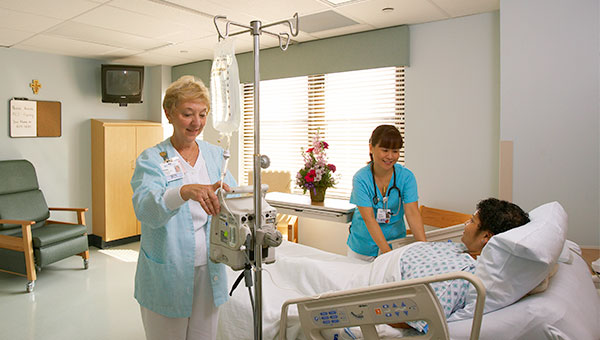 Two female nurses checking on a male patient in his hospital room