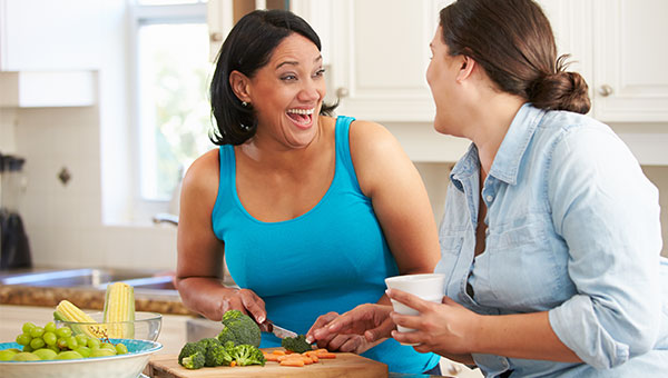 A smiling woman is preparing food while talking to her friend in the kitchen.