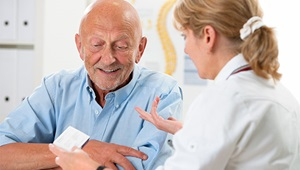 A female doctor talks with a senior male patient.