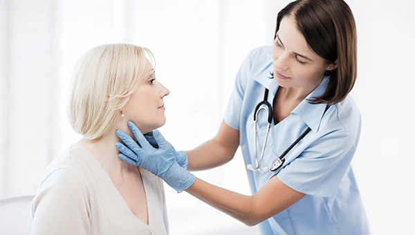A female doctor is examining the neck of a female patient.