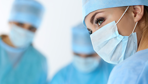 A female surgeon stands near her colleagues