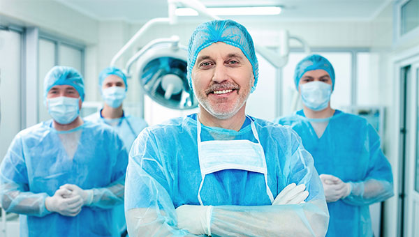 A smiling male surgeon stands near his colleagues