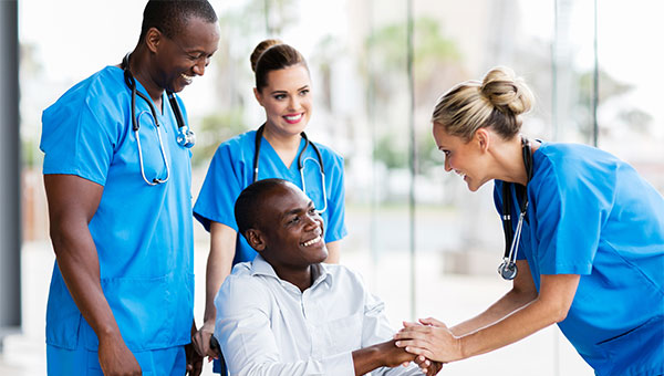 A smiling male patient talks with two female nurses and a male nurse
