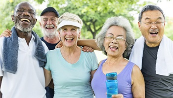 A group of senior men and women are smiling and laughing after exercising