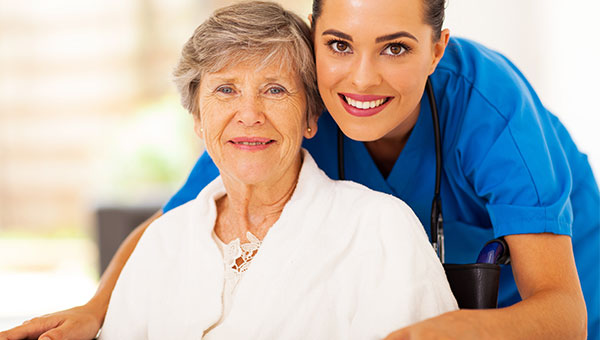 A smiling female nurse visiting with a senior female patient
