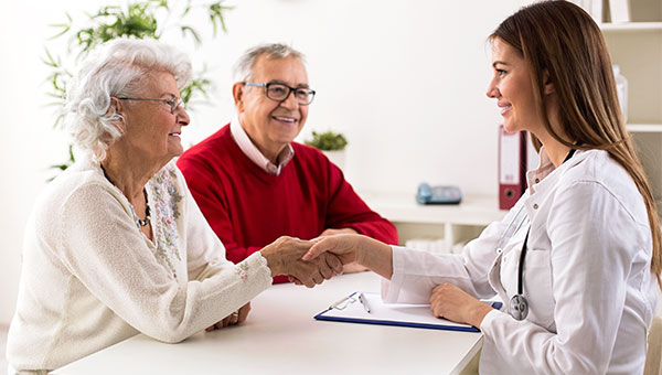 A female nurse meets with a senior couple.