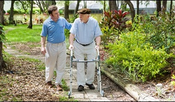 A man is walking outside next to his elderly father, who is using a walker.