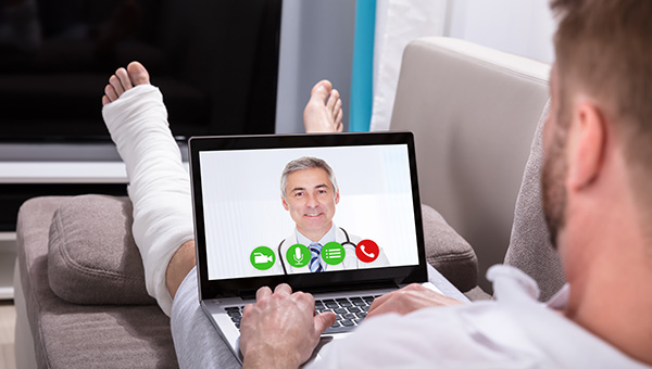 A man with a bandaged left foot, ankle and calf is resting on his sofa while talking to a doctor via video chat on his laptop.