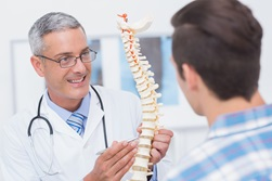 A male doctor talks to a male patient about spine health.